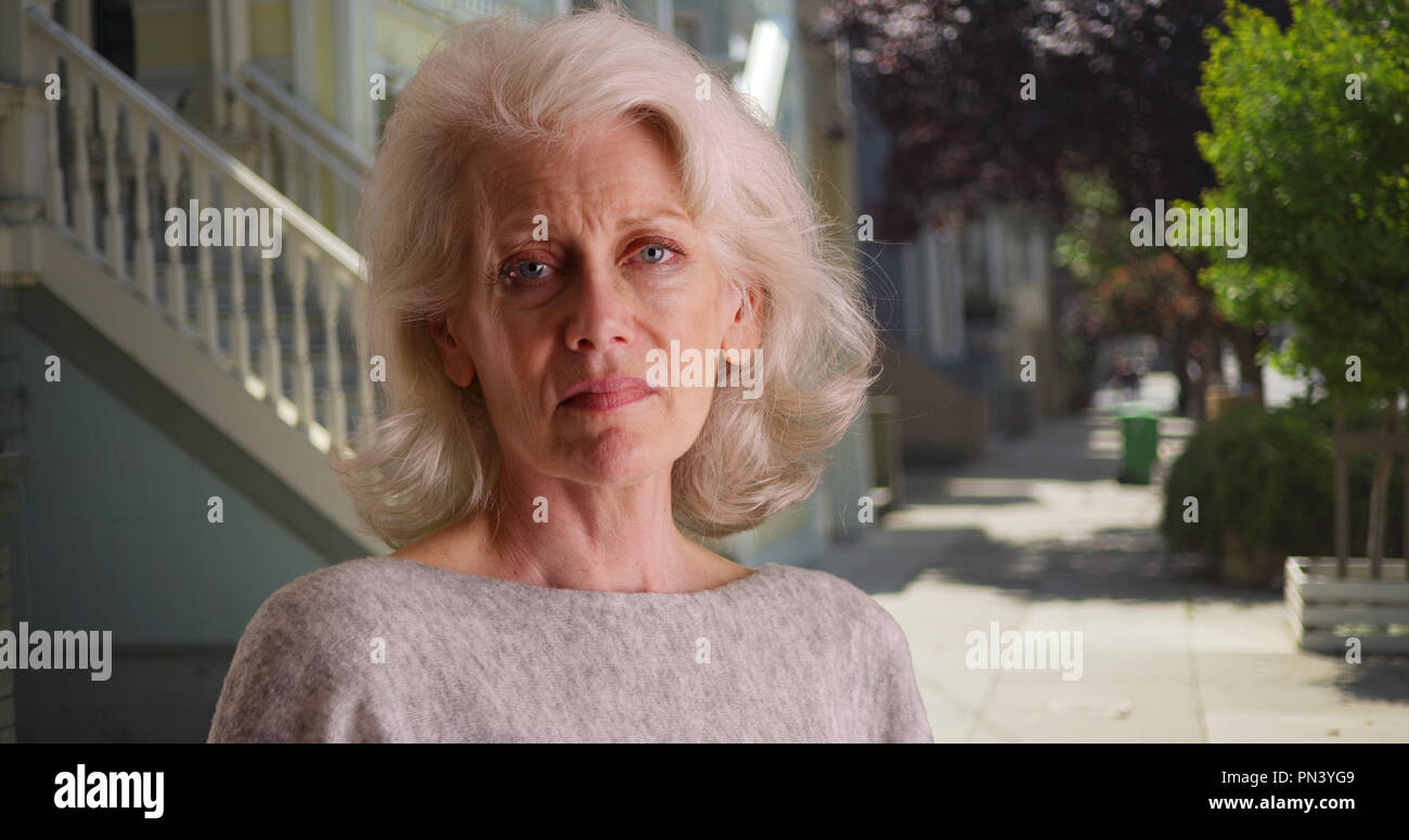 Depressed mature white woman looking sadly at camera in quiet neighborhood - Stock Image