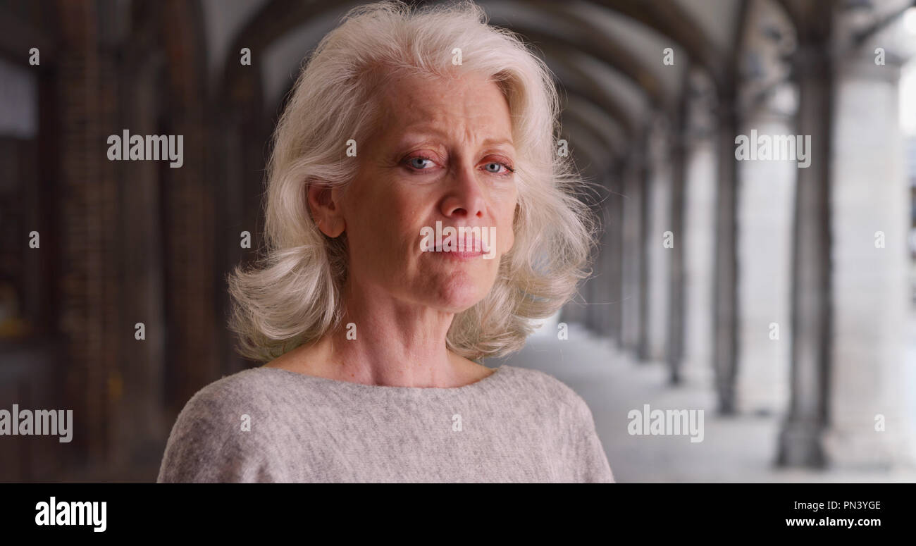 Sad older woman looking into camera standing outdoors - Stock Image