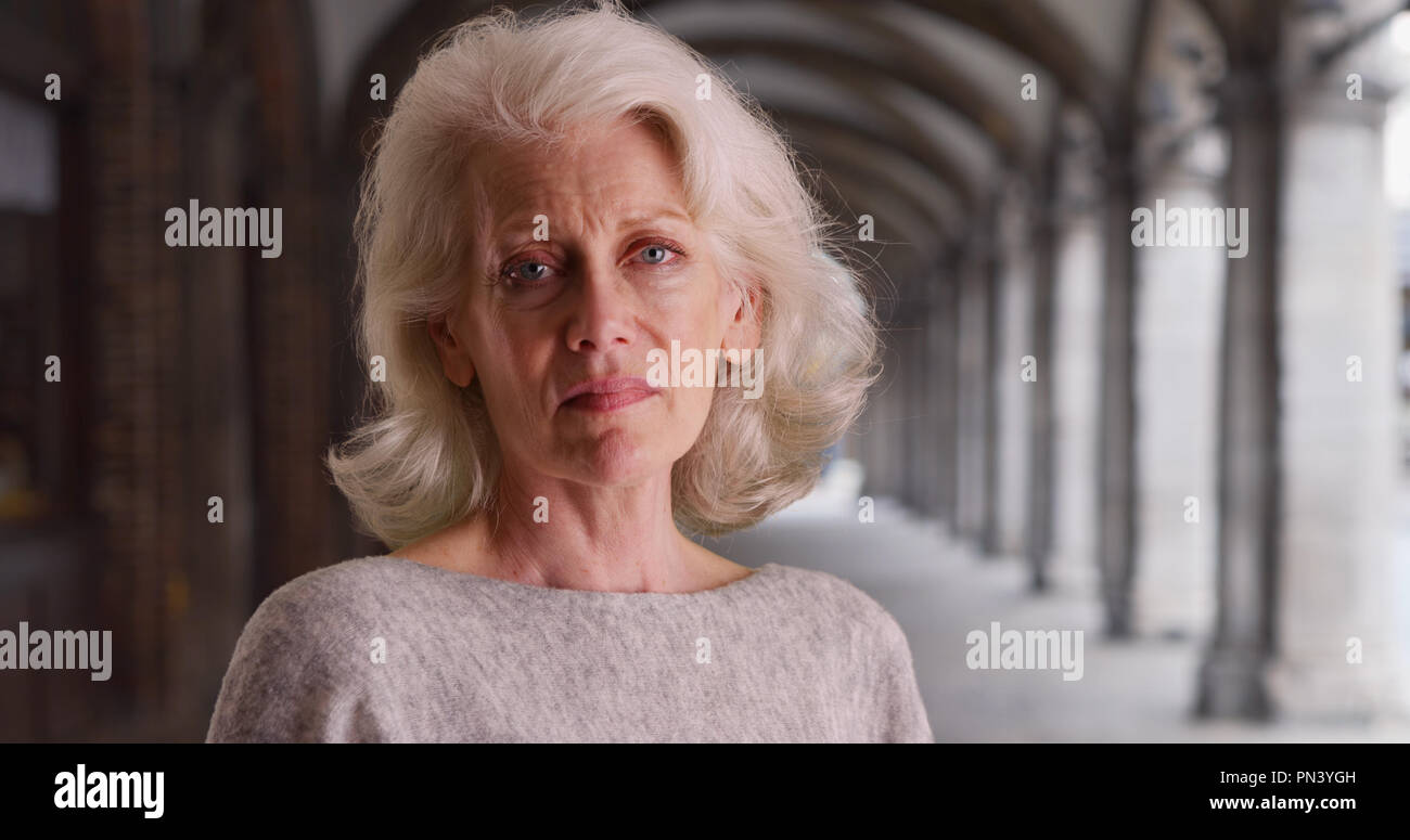 Sad older woman looking into camera then away standing outdoors - Stock Image