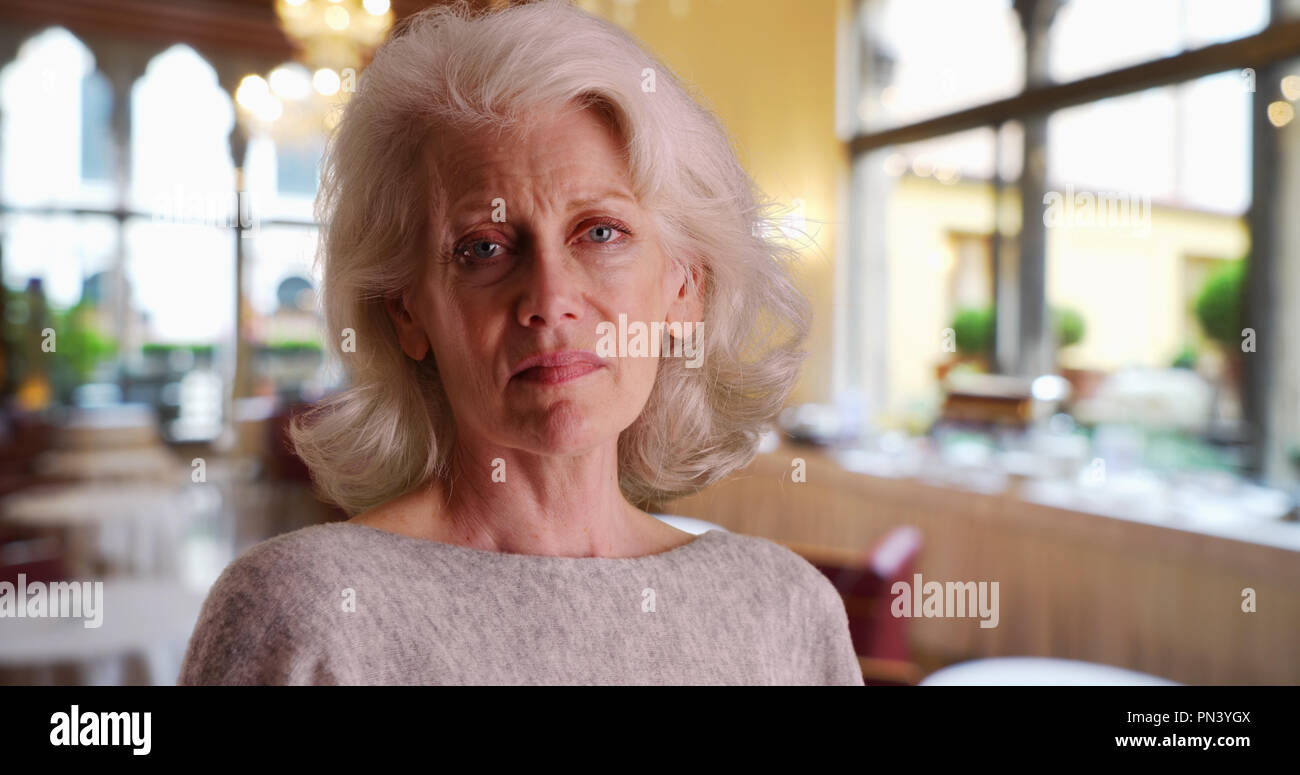 Close up of sad older woman standing in banquet hall or restaurant - Stock Image