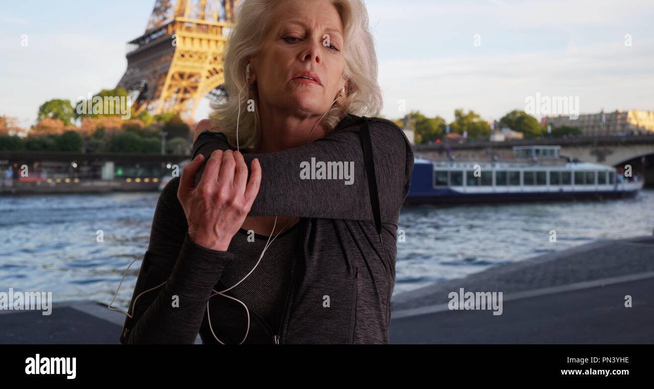 Mature woman jogger by the Seine warming up for run in Paris - Stock Image