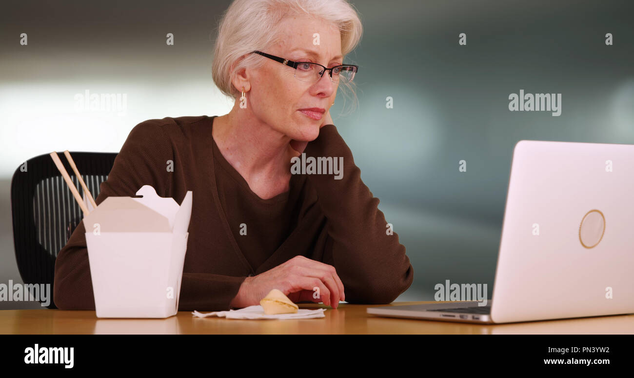 0d9f1998ed Close-up of senior woman browsing web on laptop while eating Chinese food -  Stock