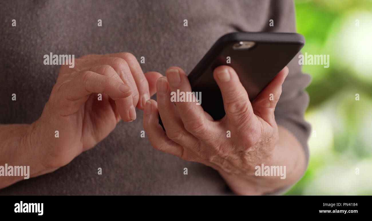 Tight shot of senior person's hands holding cell phone texting in nature setting - Stock Image