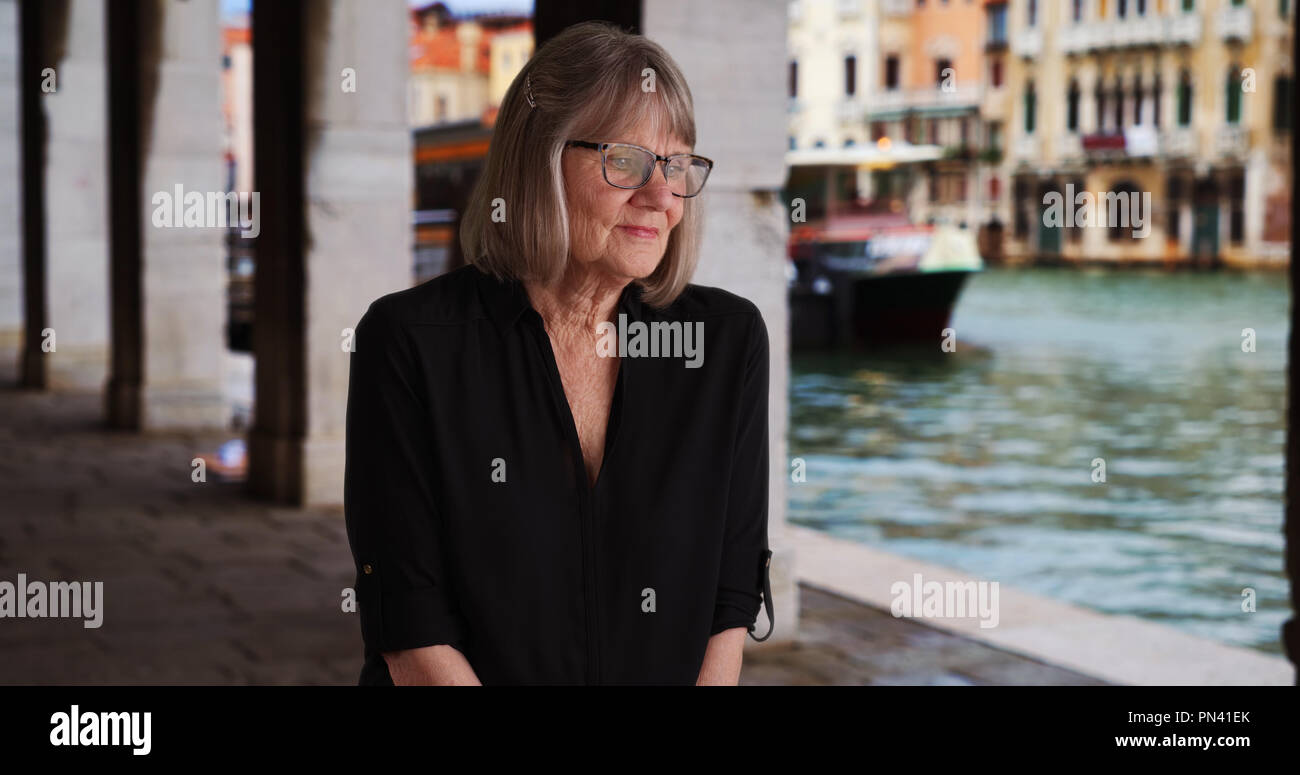Somber senior lady thinking to herself seated outdoors while in Venice Italy - Stock Image