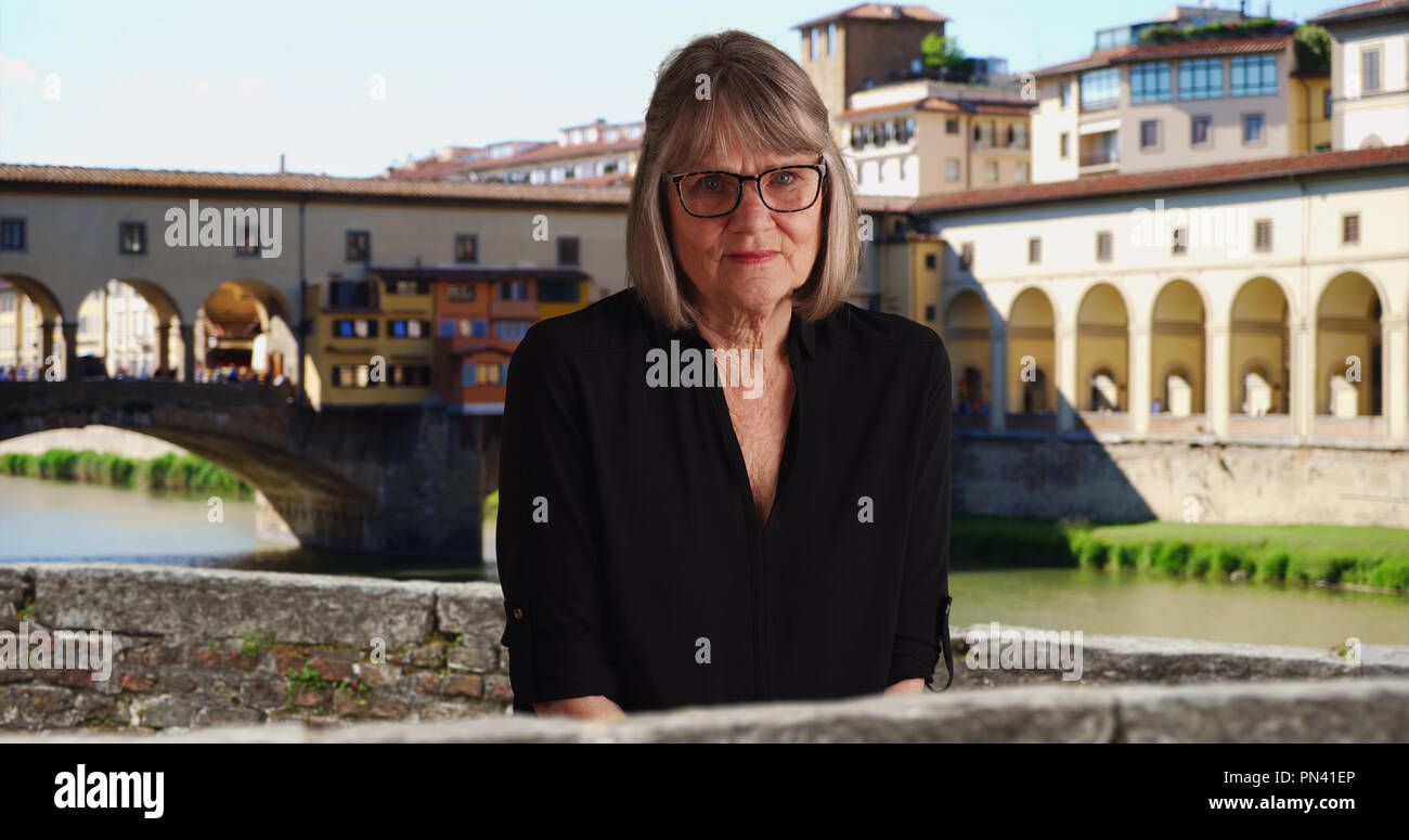 Thoughtful aged woman wearing black outfit looking at camera in Florence - Stock Image