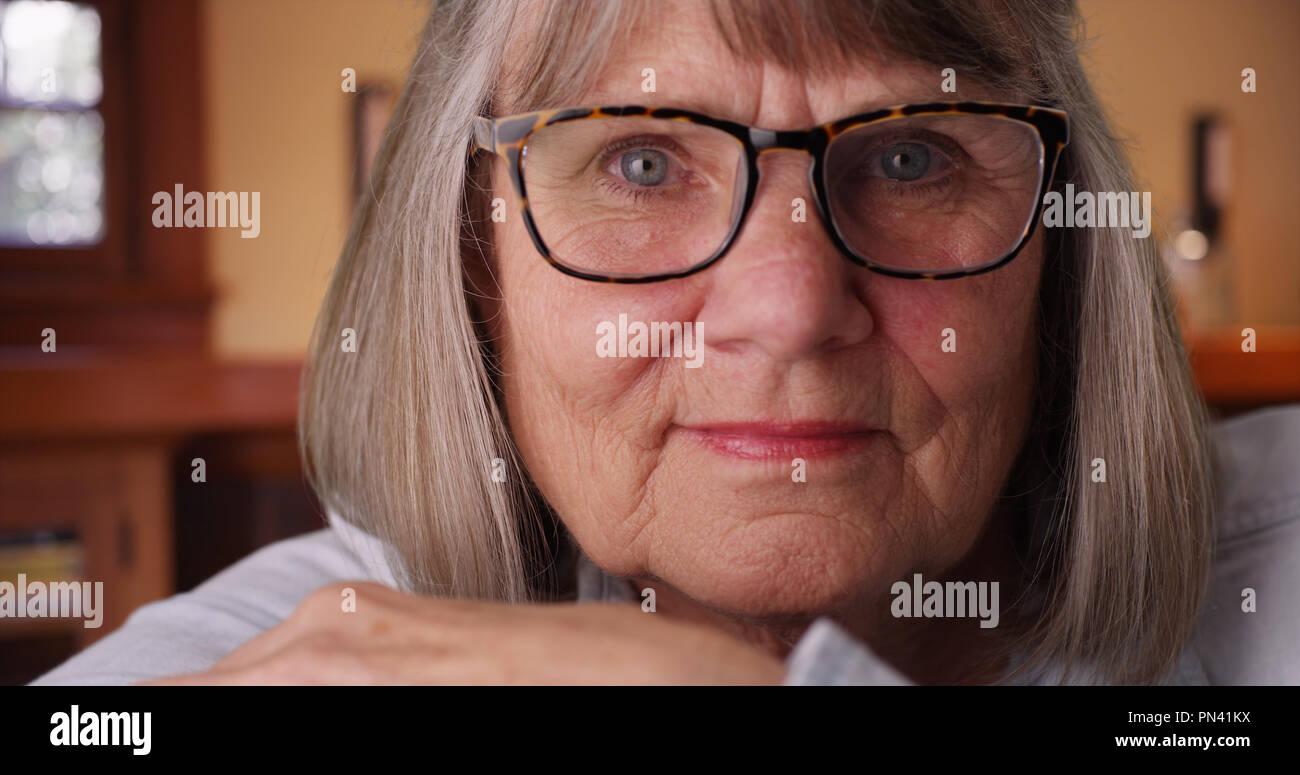 Close-up of somber elderly woman wearing eyeglasses looking at camera indoors - Stock Image