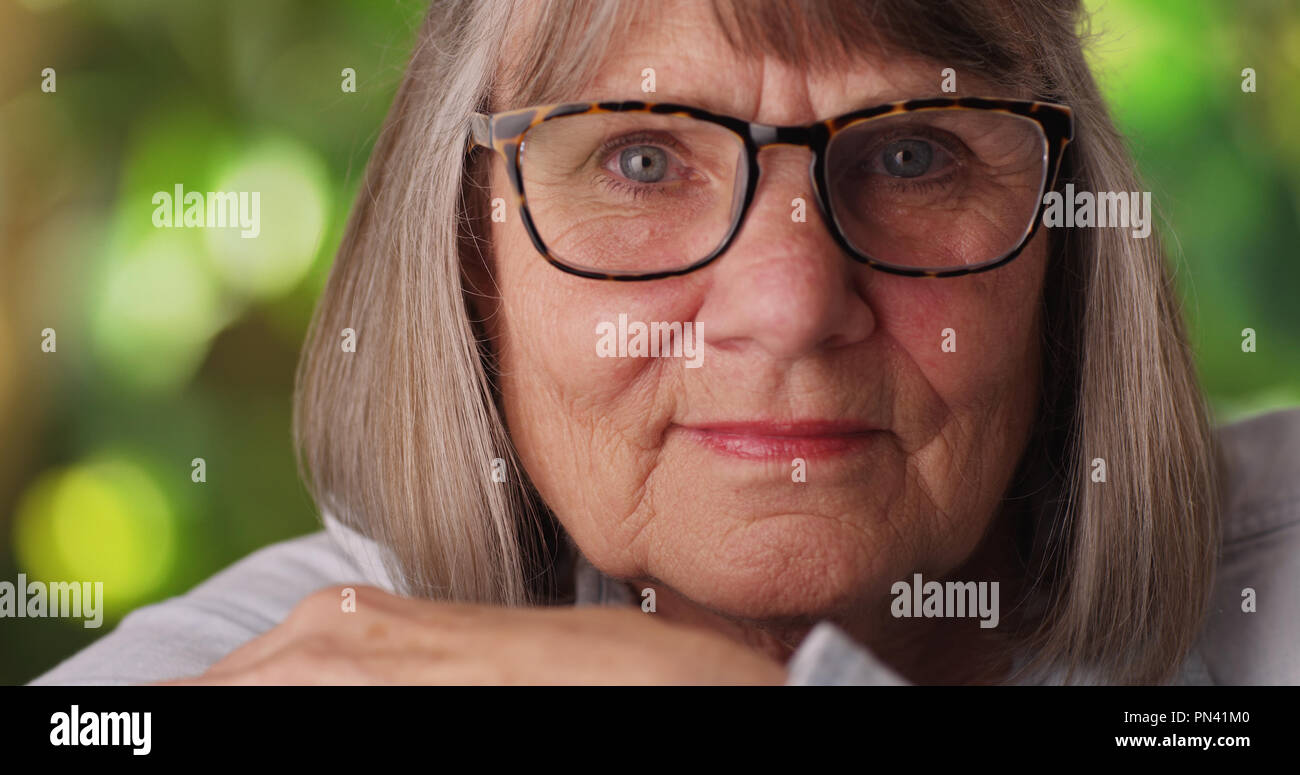 Close view of relaxed senior lady looking at camera in lush outdoor setting - Stock Image