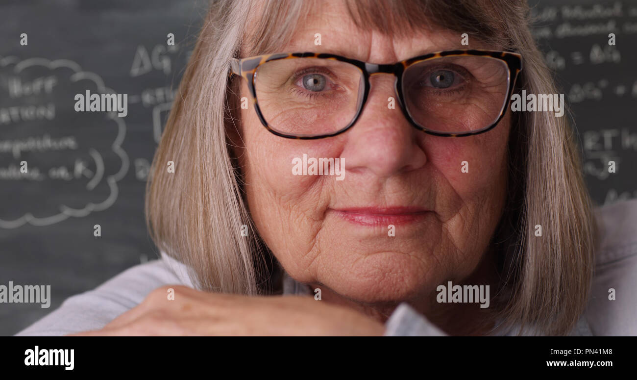 Close view of casual old female teacher looking at camera in front of chalkboard - Stock Image