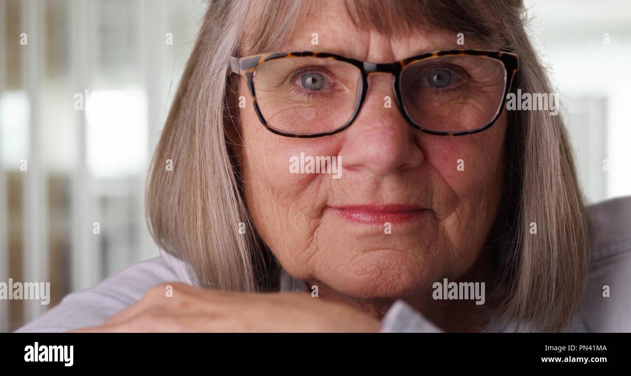 Close-up of somber elderly woman wearing eyeglasses in modern indoor setting - Stock Image
