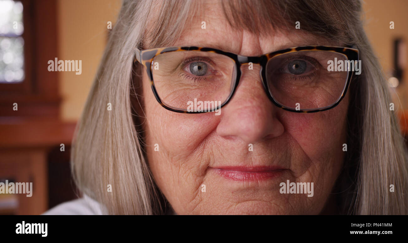 Close-up of old white woman with prescription glasses staring at camera indoors - Stock Image
