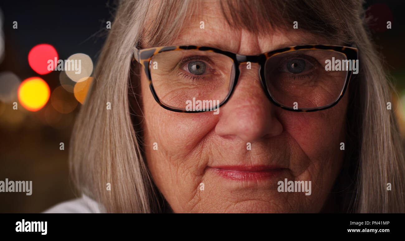 Close-up of old caucasian woman wearing glasses in city setting at night - Stock Image