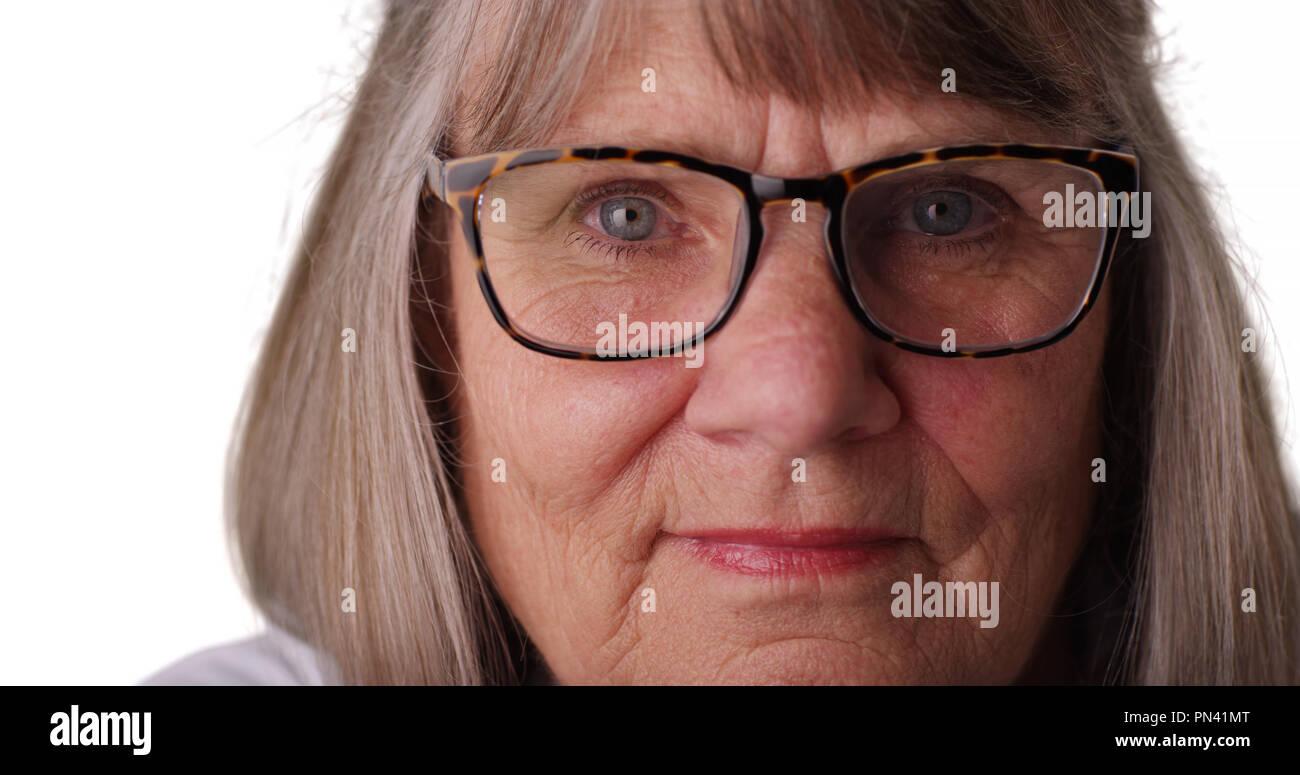 Tight shot of somber elderly woman wearing eye glasses on white background - Stock Image