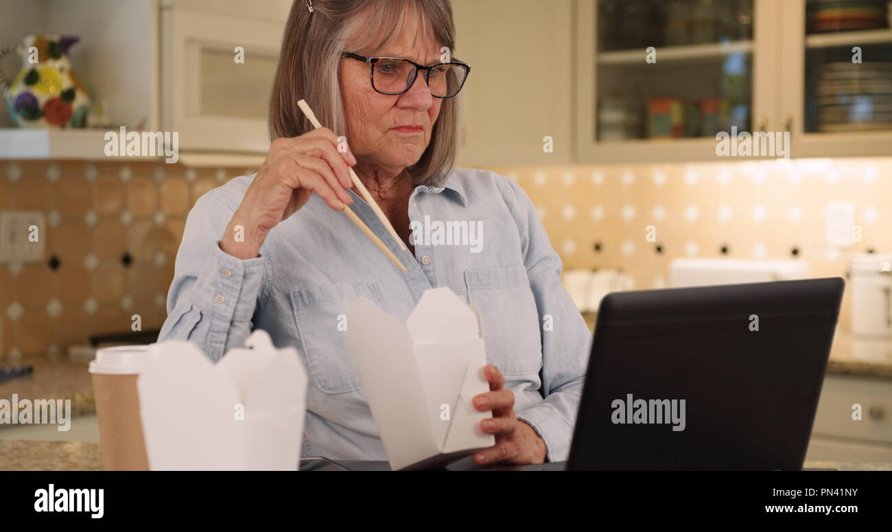 Caucasian lady eating Chinese food while on her portable computer in kitchen - Stock Image