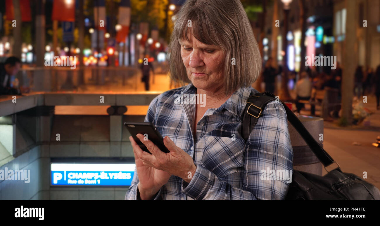Confused senior woman using smartphone device for navigation on Champs-Elysees Stock Photo