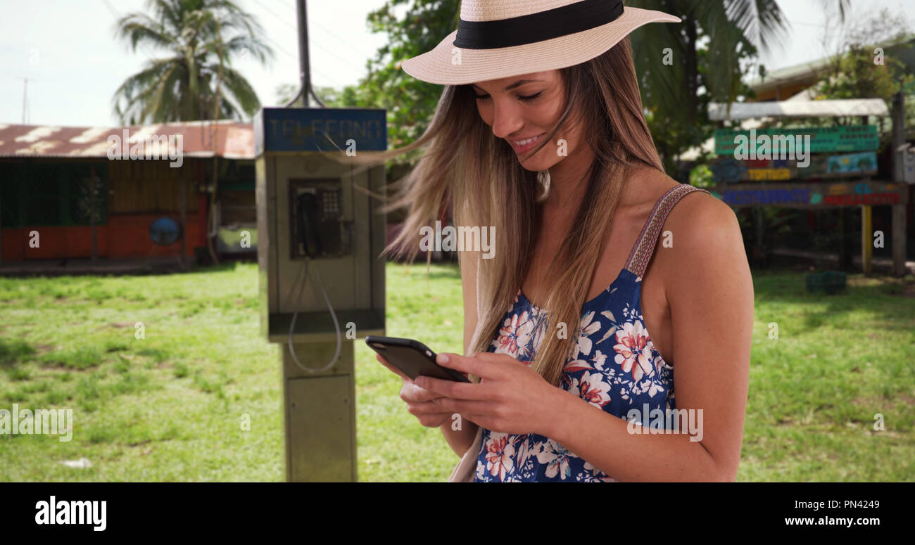 Millennial girl in her 20s text messaging on cellphone while in Costa Rica - Stock Image