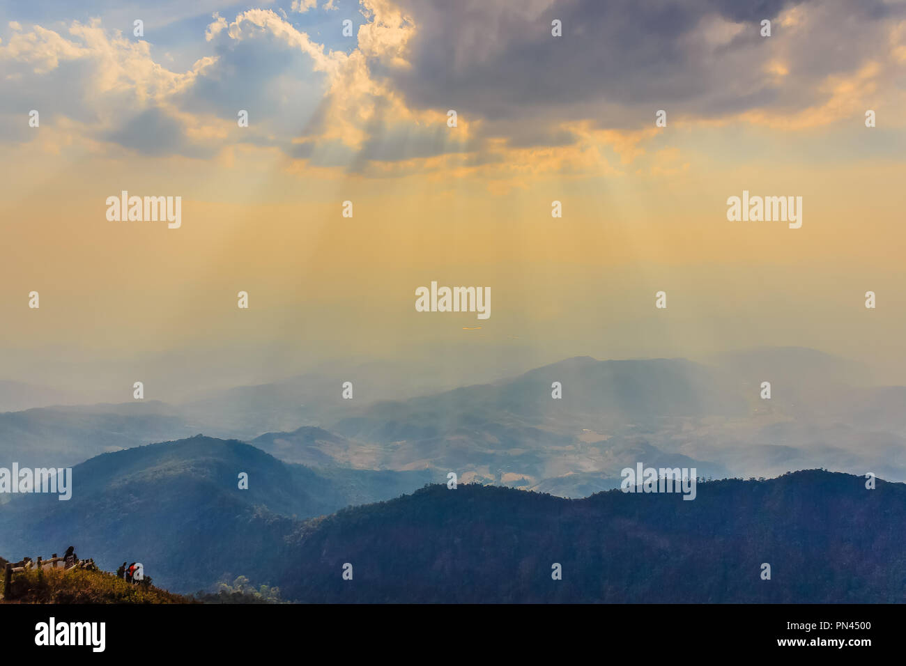Fantastic sunbeams shining through the clouds cover the mountain and tourists at Kiew Mae Pan trekking route in Doi Intanon national park, Chiang Mai, - Stock Image