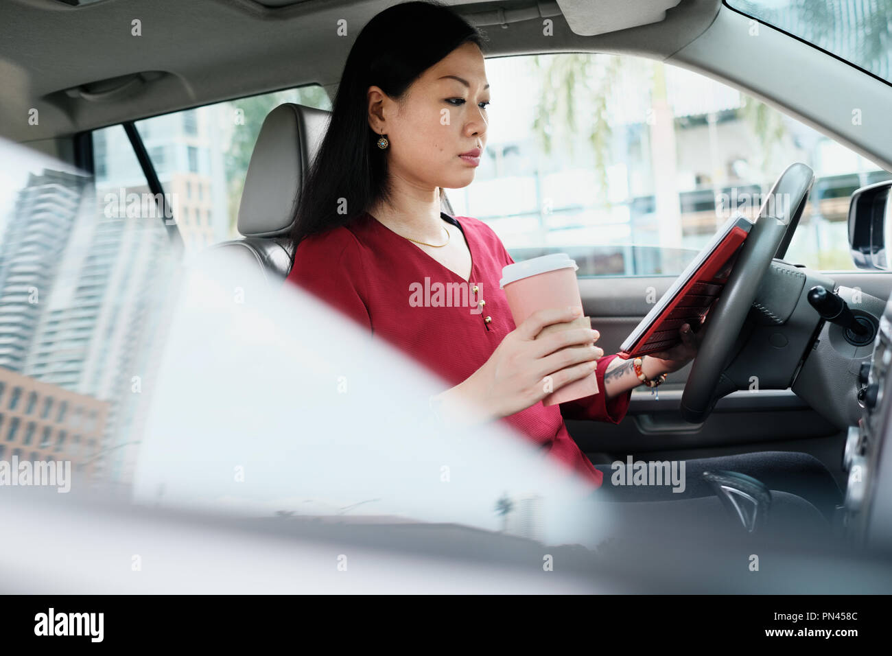 Busy Chinese Business Woman Working In Car With Tablet - Stock Image