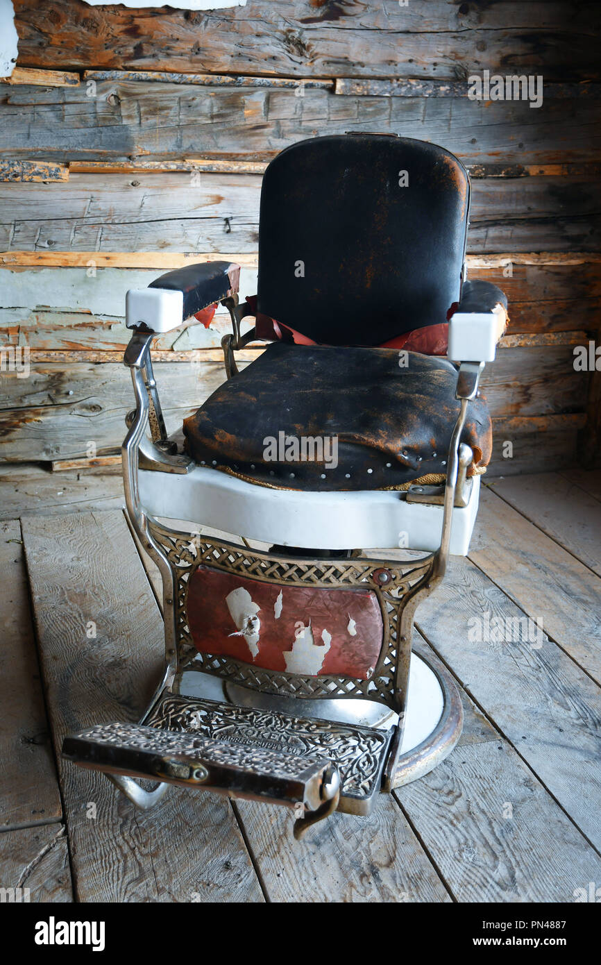 Antique barber's chair in an old log cabin Stock Photo