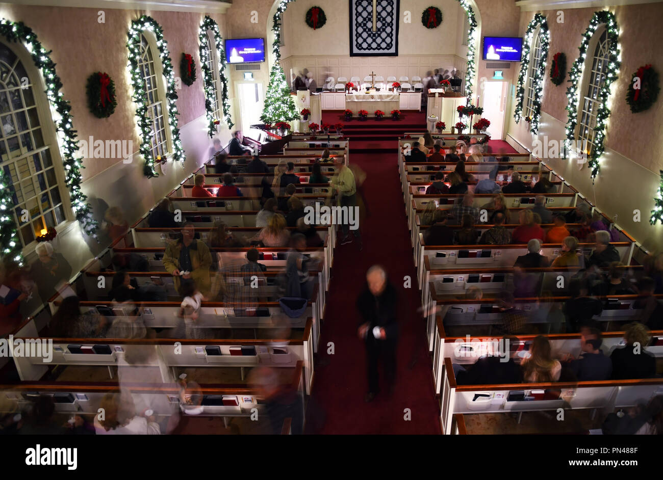 KALISPELL, MONTANA, USA - December 24, 2017: Parishners at Epworth United Methodist Church leave the pews after a Christmas Eve candlelight service Stock Photo