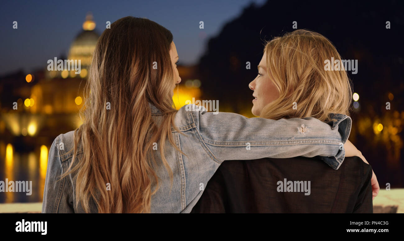 Young brunette with arm around blonde friend's shoulder in Rome Italy - Stock Image