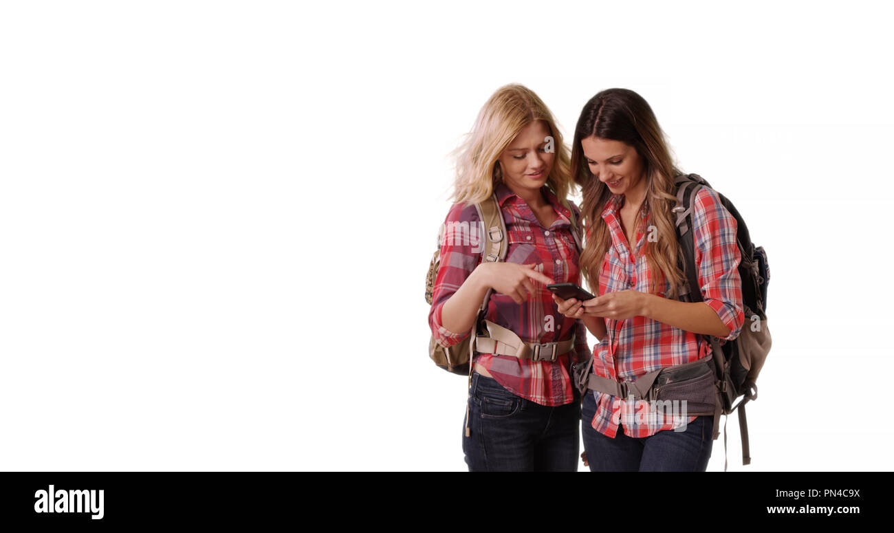 Two women backpackers using cell phone on white background with copy space - Stock Image