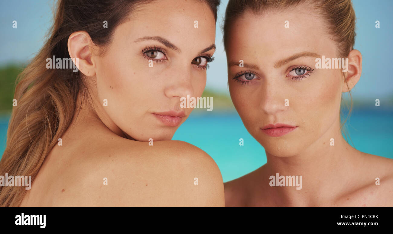 Two pretty white girls wearing makeup gazing intently at camera outside at beach - Stock Image