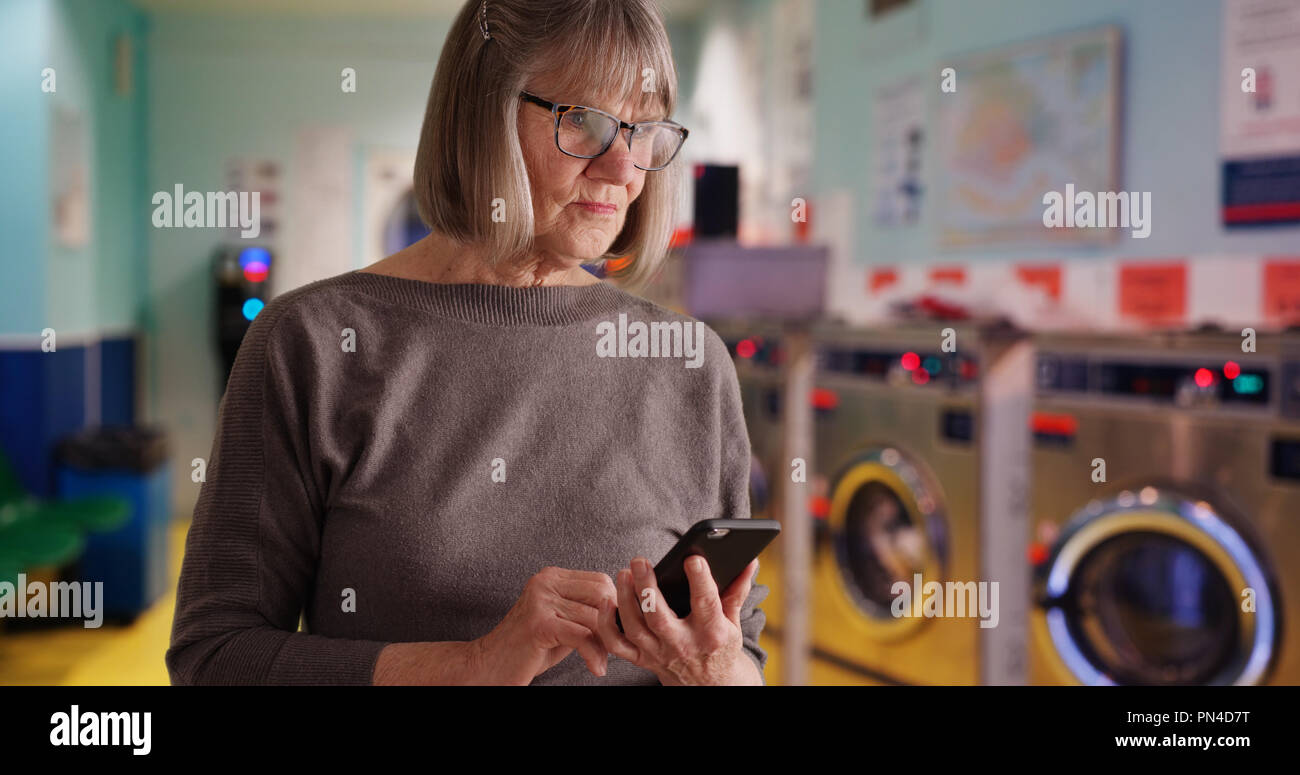 Somber old lady reading distressing news alone at laundromat - Stock Image