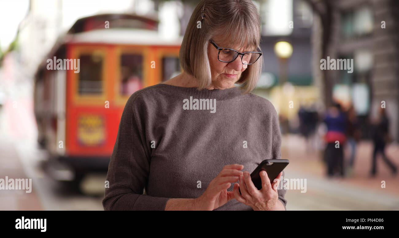 Somber Caucasian lady reading distressing e-mail on phone near trolley outside - Stock Image