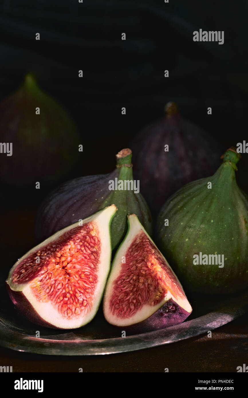 quartered green figs on dark background, space for your text - Stock Image