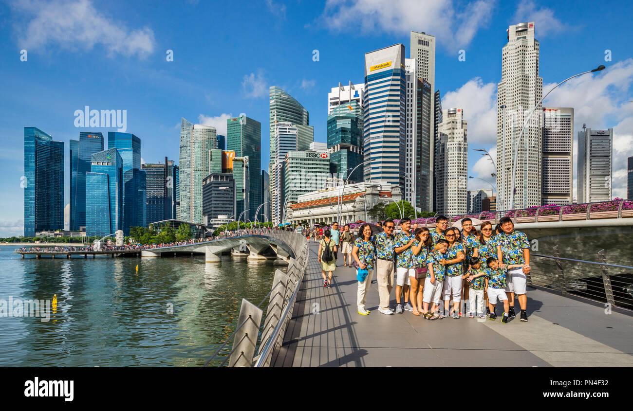 family group photo on Jubilee Bridge against the backdrop of the Singapore skyline - Stock Image