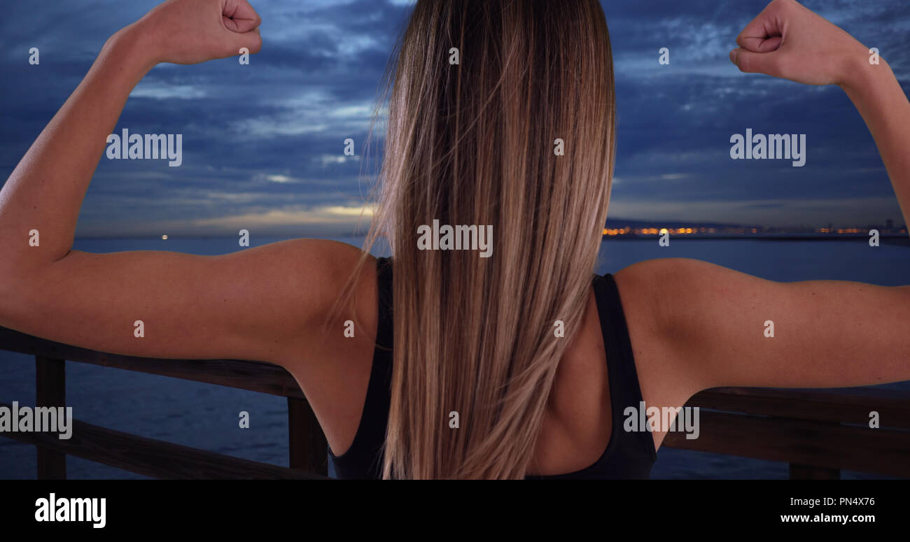 Healthy White Girl In Her 20s Showing Off Bicep Muscles Outside By
