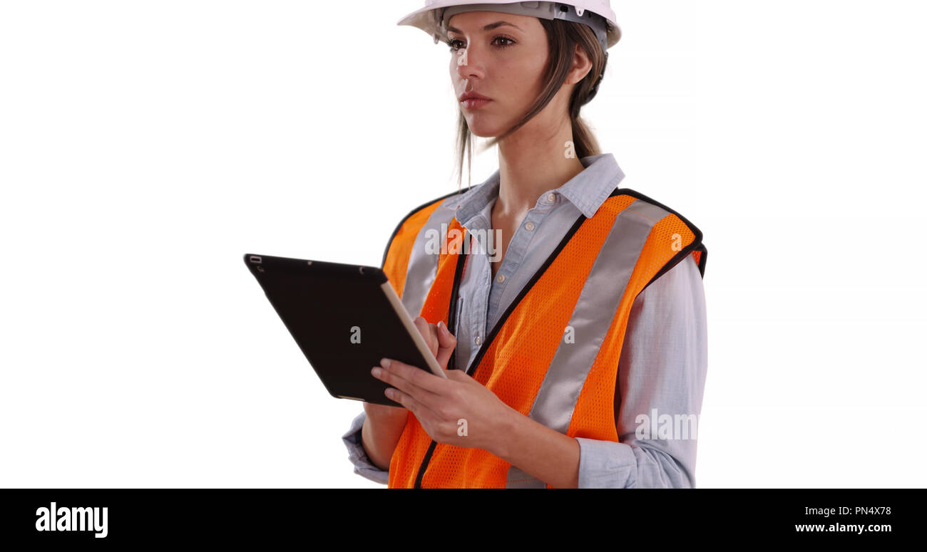 Woman wearing orange vest and hardhat working on tablet on white background - Stock Image