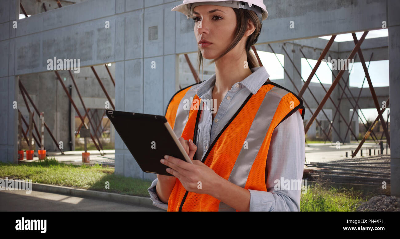 Woman in orange vest and hardhat working on tablet device at construction site - Stock Image