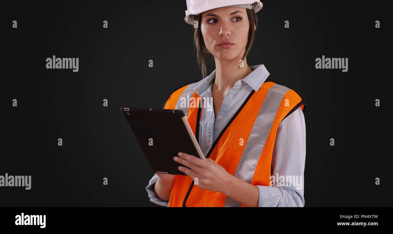 Woman in orange vest and hardhat working on tablet on solid gray background - Stock Image