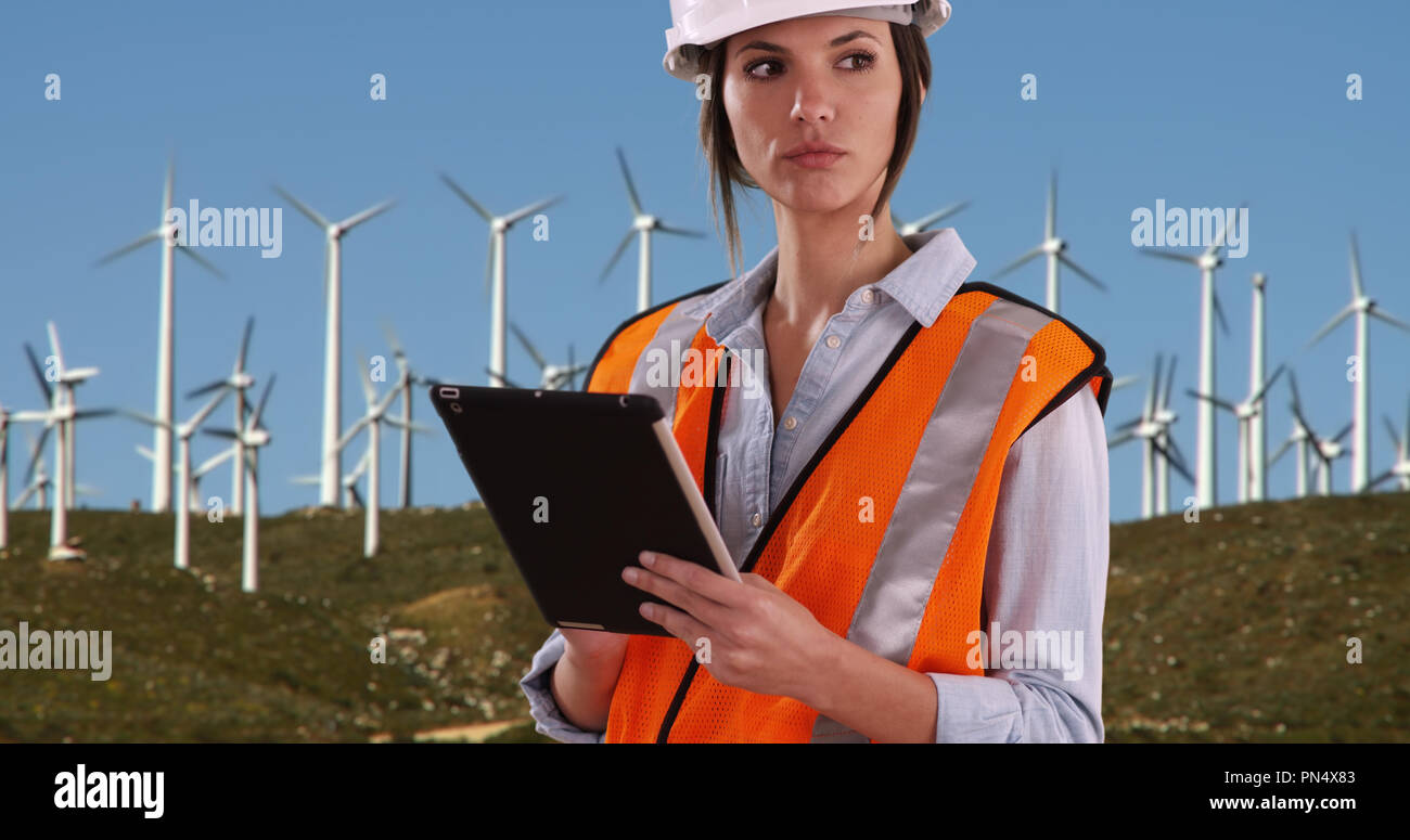 Woman in orange vest and hardhat working on tablet by wind turbines outdoors - Stock Image