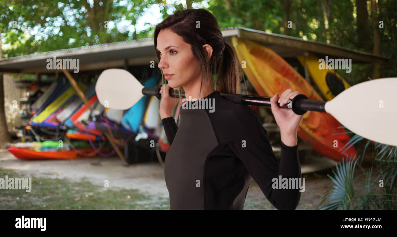 Woman in wetsuit with paddle over shoulders facing side by shack of kayaks - Stock Image