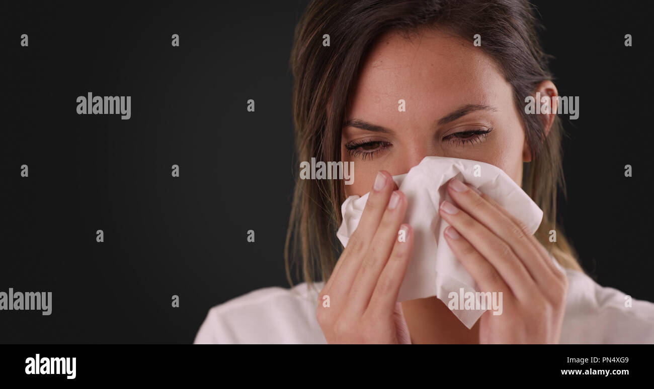 Sick Caucasian woman blowing nose into tissue paper on dark gray background - Stock Image