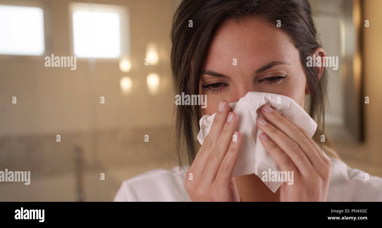 Sick Caucasian woman blowing nose into tissue paper in clean bathroom setting - Stock Image