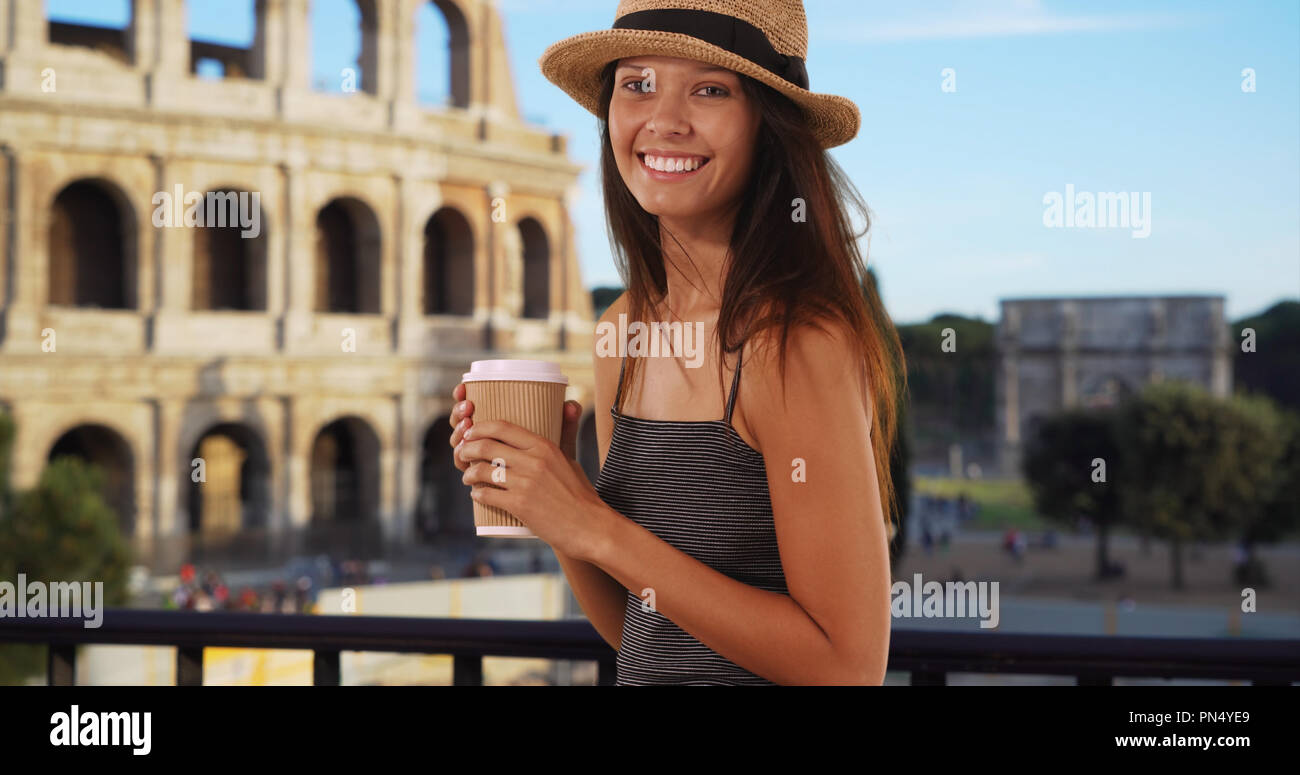 Beautiful young tourist woman with coffee standing near the Roman Coliseum Stock Photo