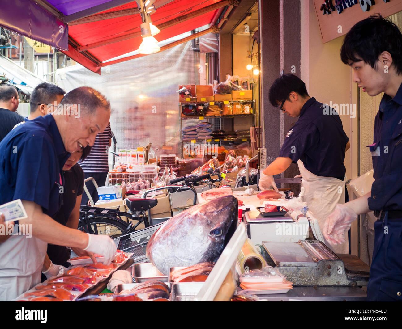 Fish mongers work with tuna at the Tsukiji Fish Market (Tsukiji outer market) in Tsukiji, Tokyo, Japan. Stock Photo