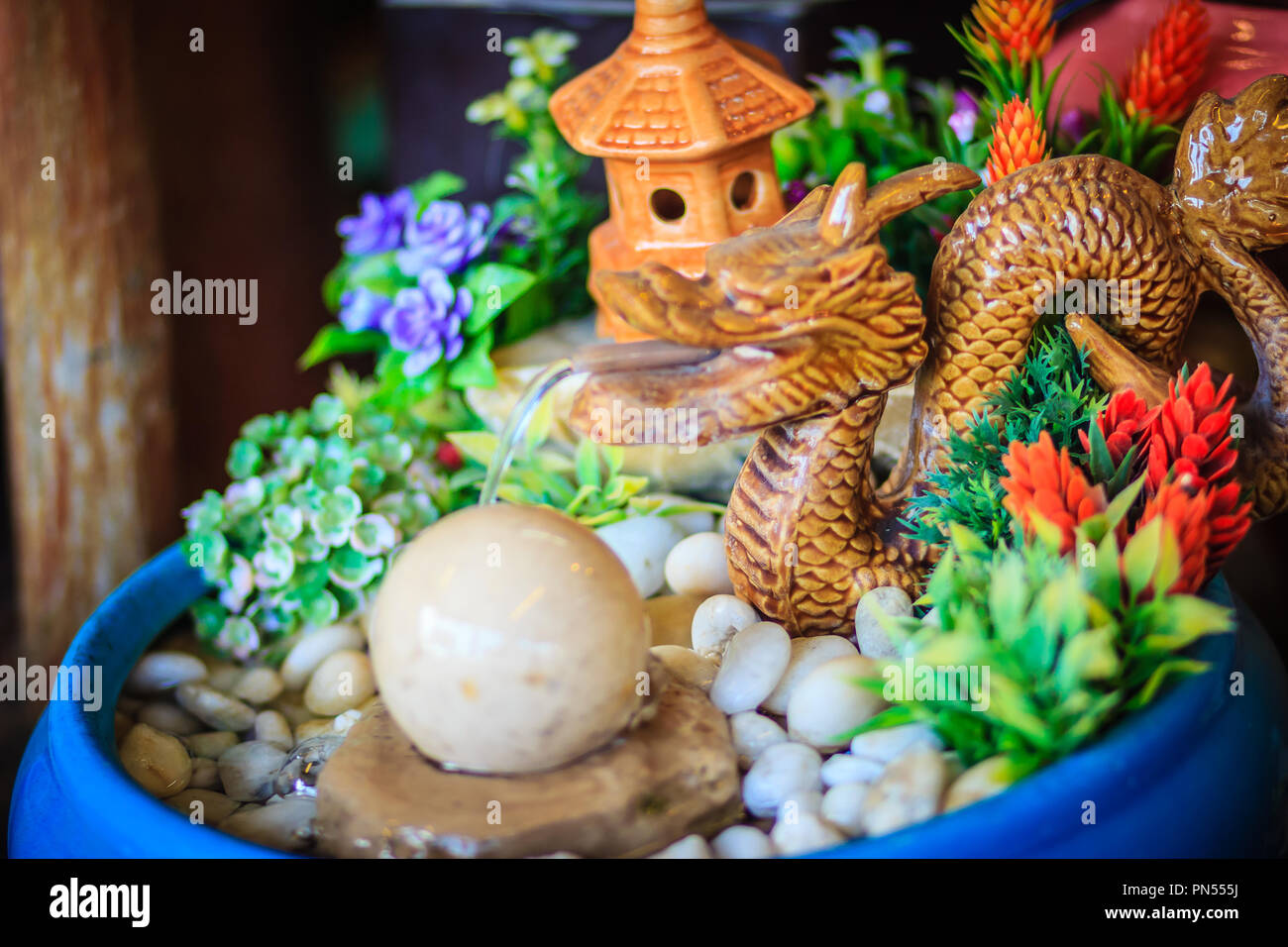 Mini fountain for garden decoration with dragon splash and jet of water to rolling stone ball. Selective focus - Stock Image