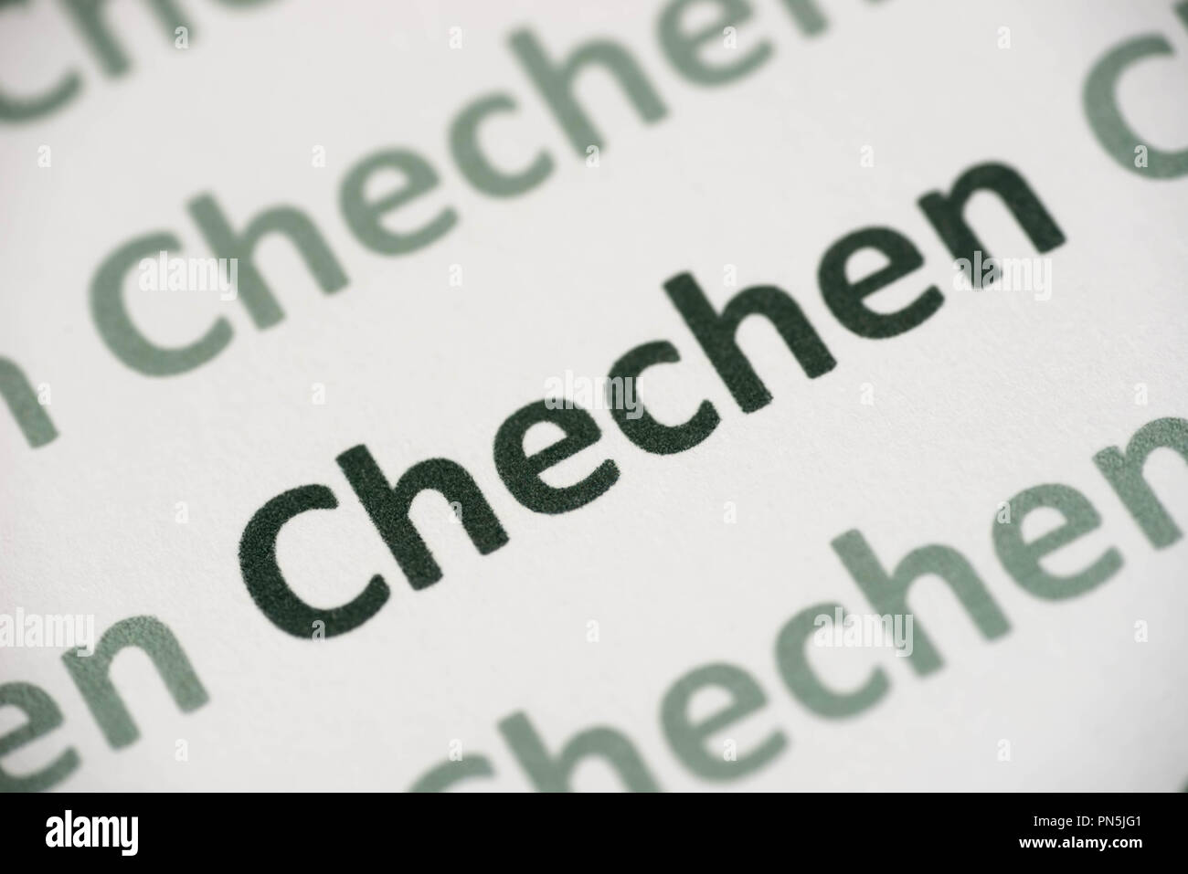 word Chechen language printed on white paper macro - Stock Image