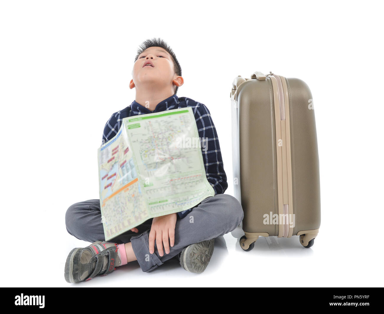 Asian boy holding map and sitting with luggage, isolated on white. - Stock Image