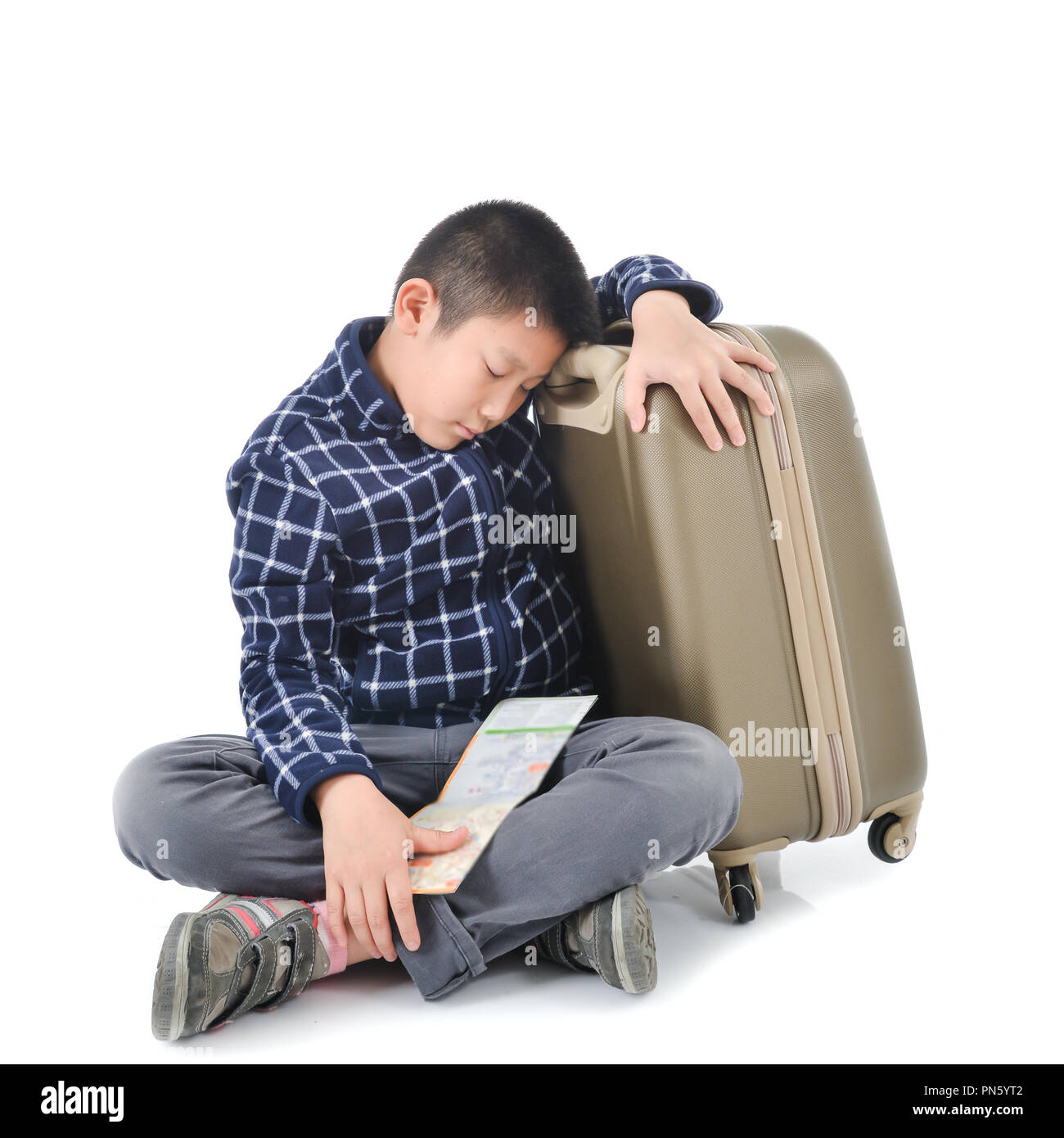Asian boy sleeping with map and luggage on white background. - Stock Image