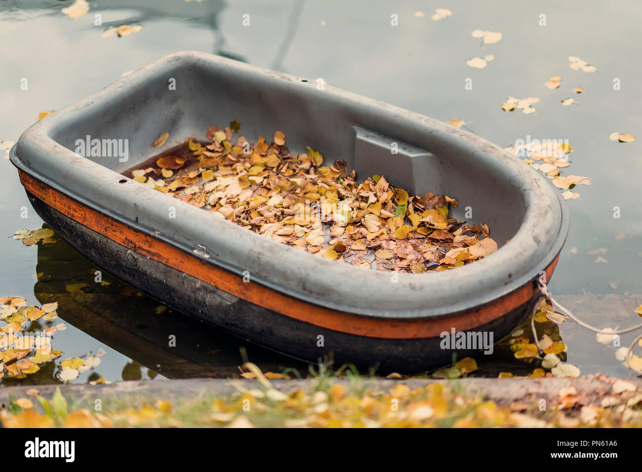 Moored dirty boat in the autumn pond. Autumn scene, fallen yellow leaves on the shore, real scene, romantic seasonal mood, concept of nostalgia - Stock Image