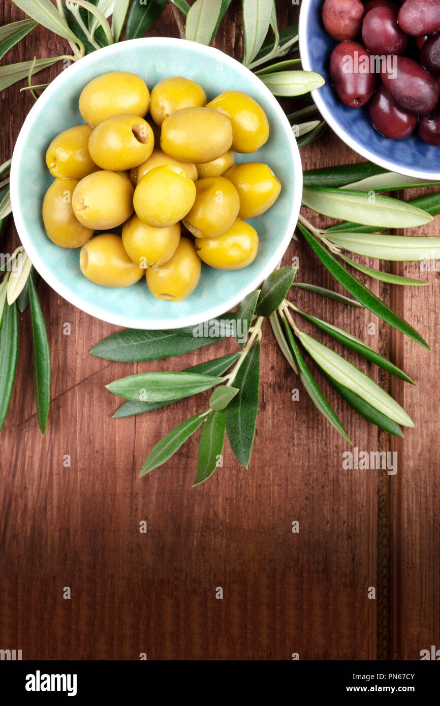 Overhead photo of various olives in bowls with a place for text - Stock Image