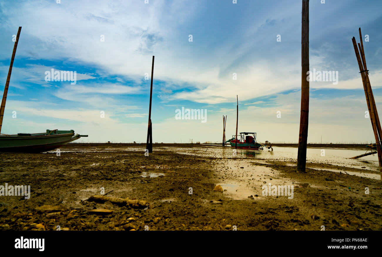 Landscape of sea at tide and blue sky and clouds with fisherman's boat. Sea mud beach when the water lower. Fishing boat parked at the shore. Lifestyl - Stock Image