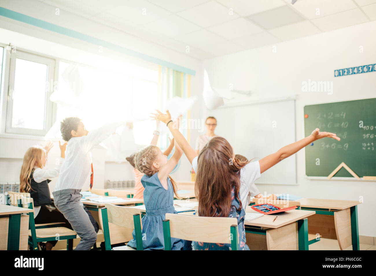 school kids have fun in class and throwing paper in air - Stock Image