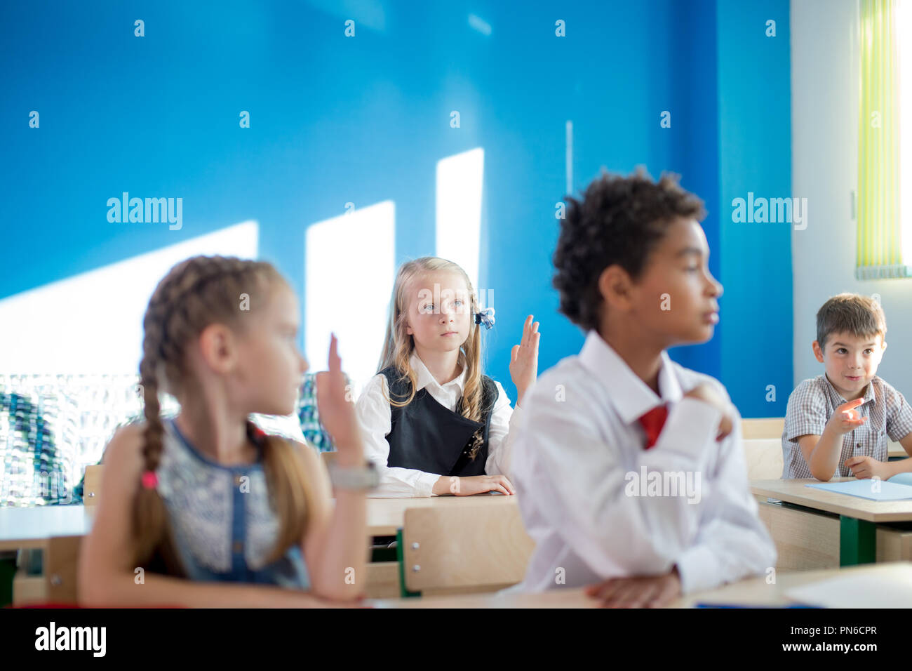 group of school children all raising their hands in the air to answer Stock Photo