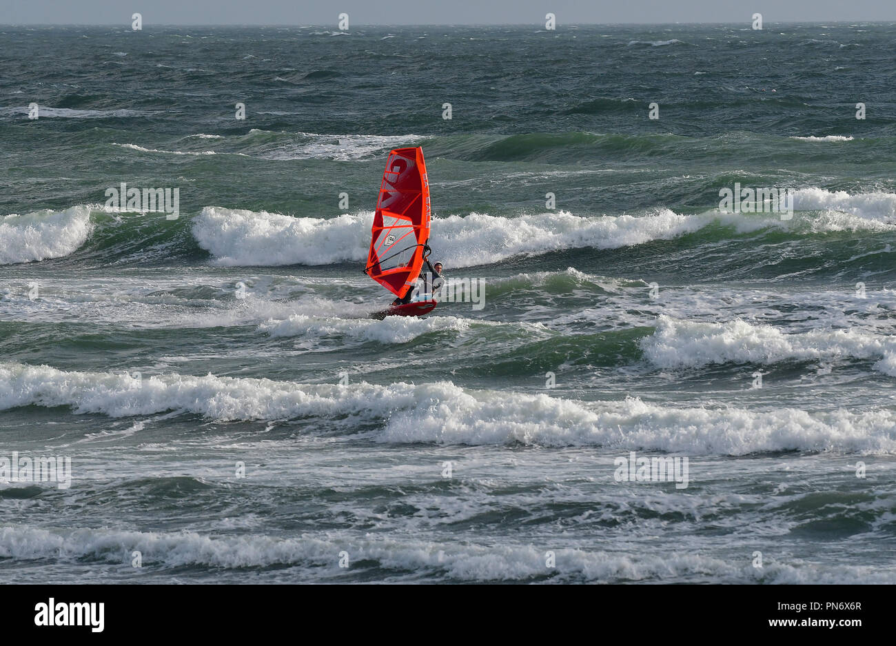 East Wittering, UK. 19th September 2018. Windsurfer(s )brave wild, wet and windy weather  of Storm Ail - our first named storm of the season. Weather was  recorded at the Chichester Bar at 3pm BST  a mean speed of 29 Knots highest gusting  35 .4 Knots The Met Office have issued an yellow weather warning for this area with strong winds and heavy rainfall.Credit Gary Blake / Alamy Live News Stock Photo